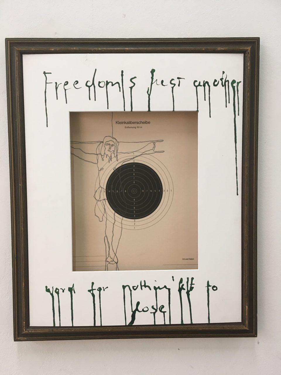 """Zeichnung auf Kleinkaliberscheibe, gerahmt, beschriftet mit """"Freedom is just another word for nothing left to lose"""""""